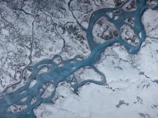 Questa immagine aerea della Groenlandia mostra i fiumi d'acqua causati dal disgelo e le aree di ghiaccio più scuro descritte dall'articolo. la superficie della Groenlandia sta assorbendo più radiazione solare e i processdi di fusione sono proporzionali alle dimensioni dei grani di ghiaccio e alle impurità liberate. Credit: Marco Tedesco / Lamont-Doherty Earth Observatory
